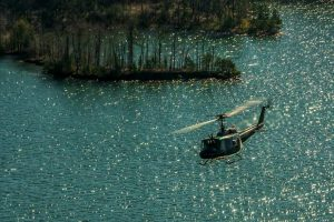 Huey UH-1 over water.